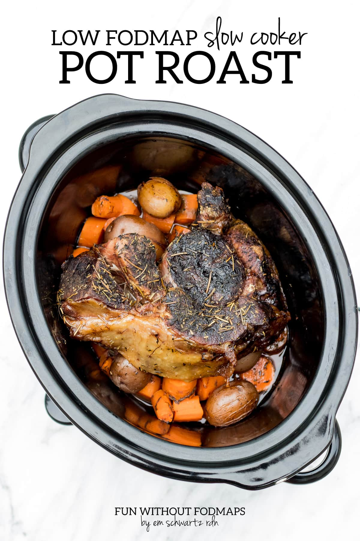 "Beef roast, carrots, and potatoes cooked in a slow cooker are sitting on a white marble surface. Above, a black text overlay reads ""Low FODMAP Slow Cooker Pot Roast""."