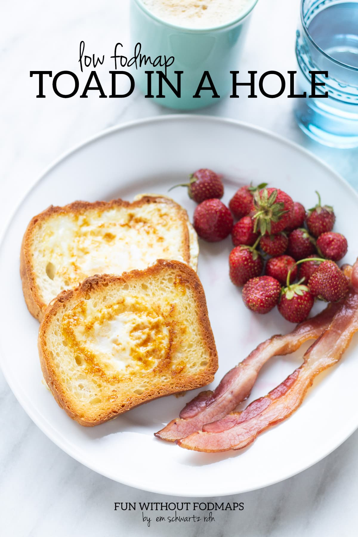 """A plate with two pieces of toast with eggs cooked into the center of them. Bacon and strawberries sit on the side. Above the plate, black text reads """"Low FODMAP Toad in a Hole""""."""