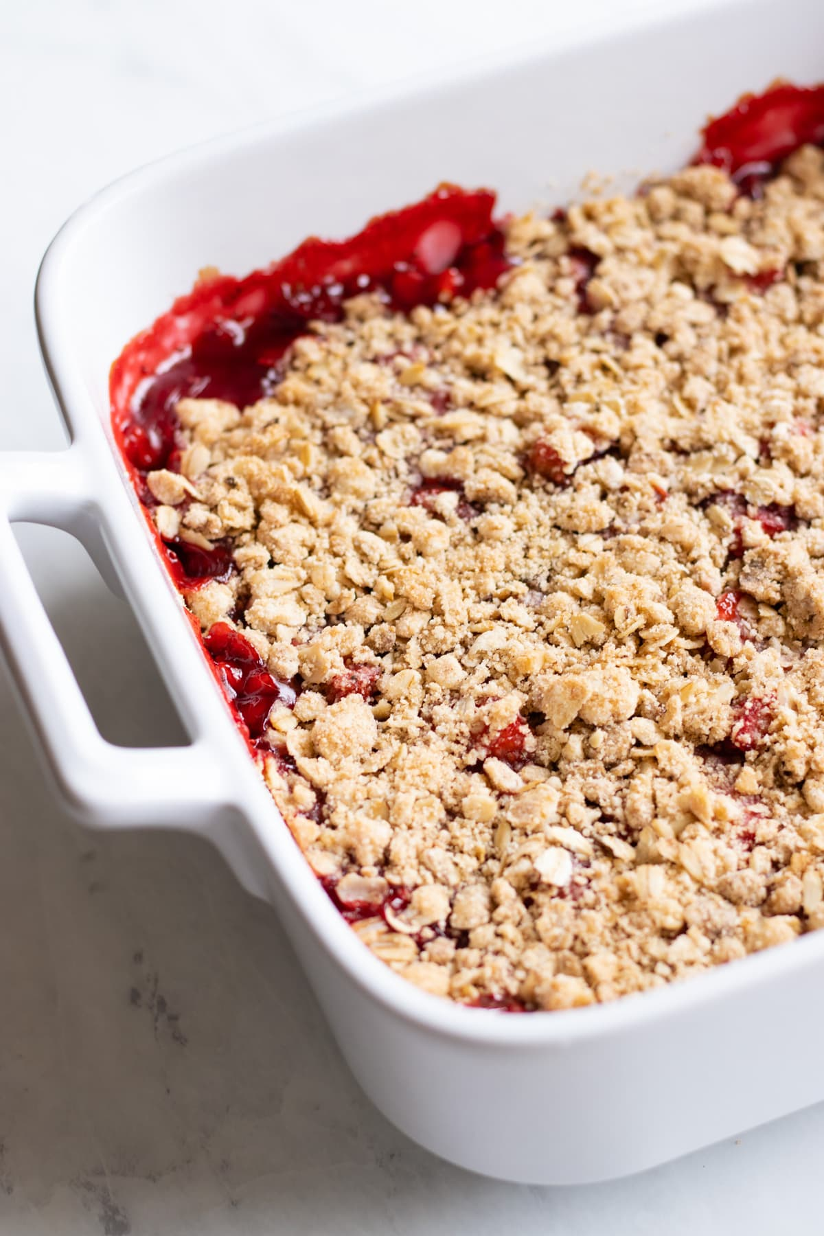 Baked strawberry-rhubarb crumble in a white baking dish.