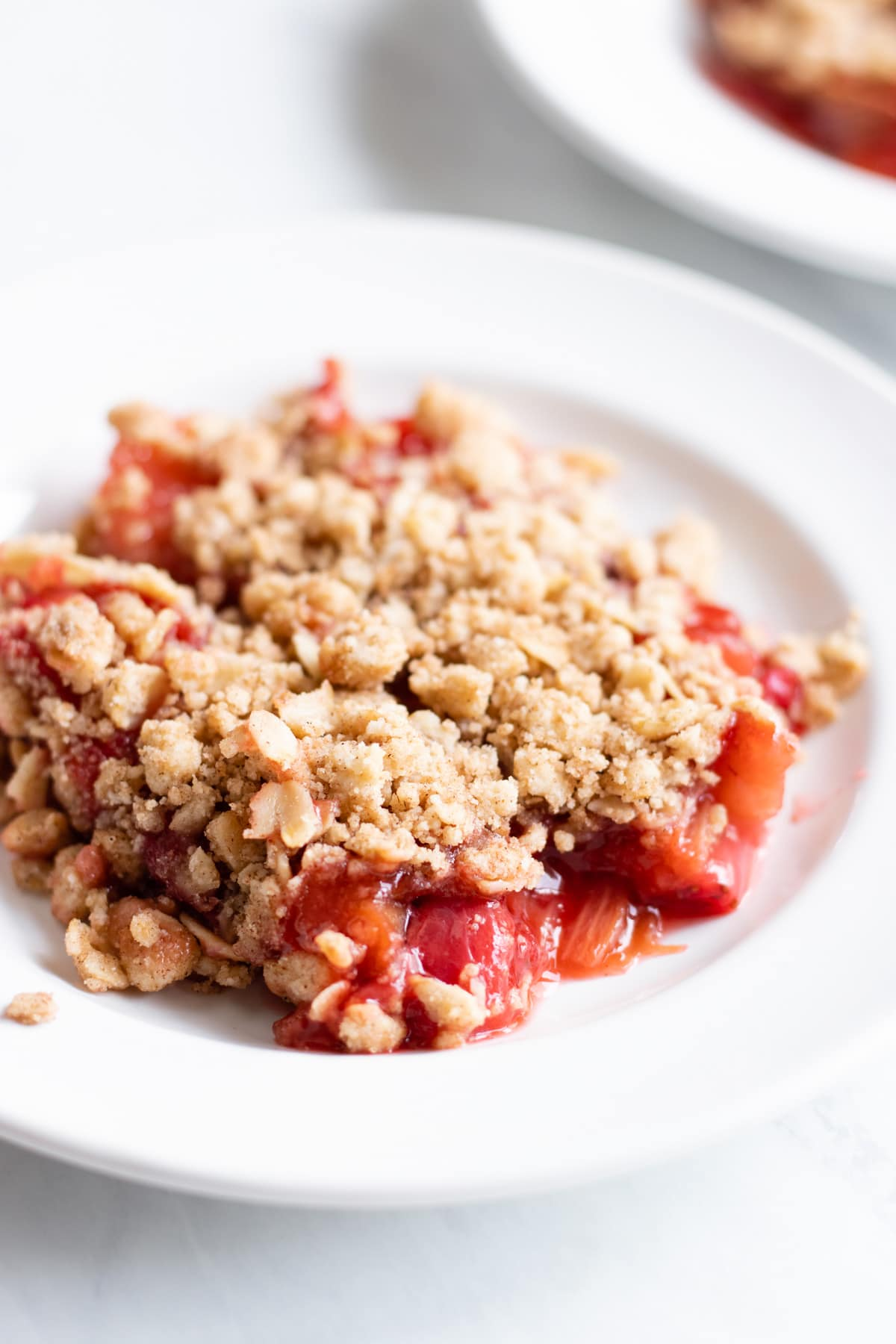 A close up of gooey baked strawberry-rhubarb topped with an oat crumble.