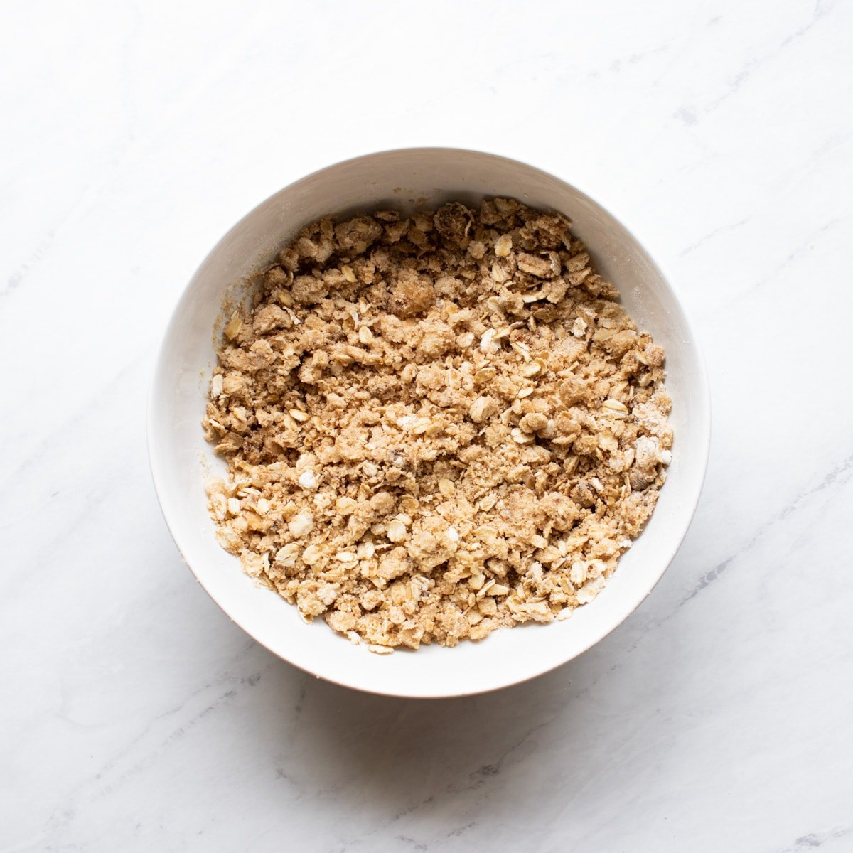 Flour, oats, brown sugar, cinnamon, and melted butter have been mixed until crumbly.
