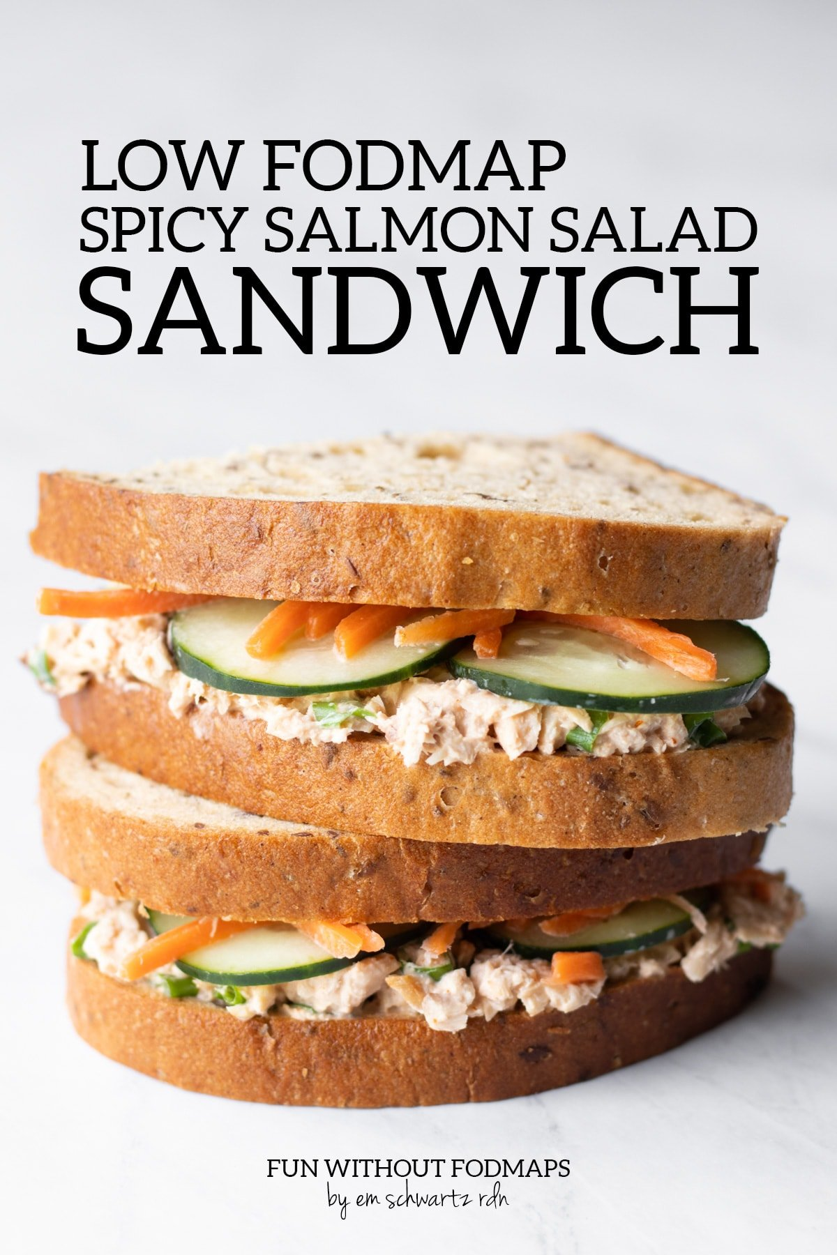 "Halves of a spicy salmon salad sandwich are stacked on top of one another. There are bits of cucumber slices and carrot matchsticks peeking out in between the bread and the salmon spread. Above the stacked sandwich, black text reads ""Low FODMAP Spicy Salmon Salad Sandwich"". Below the sandwich in small black text, it says ""FUN WITHOUT FODMAPS by Em Schwartz RDN"""