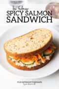 """Sandwich on a plate with a small bowl of red grapes and a glass of watA sandwich stuffed with salmon salad, cucumber slices, and shredded carrots sits on a plate. Above the plate, a black text overlay reads """"Low FODMAP Spicy Salmon Sandwich."""""""