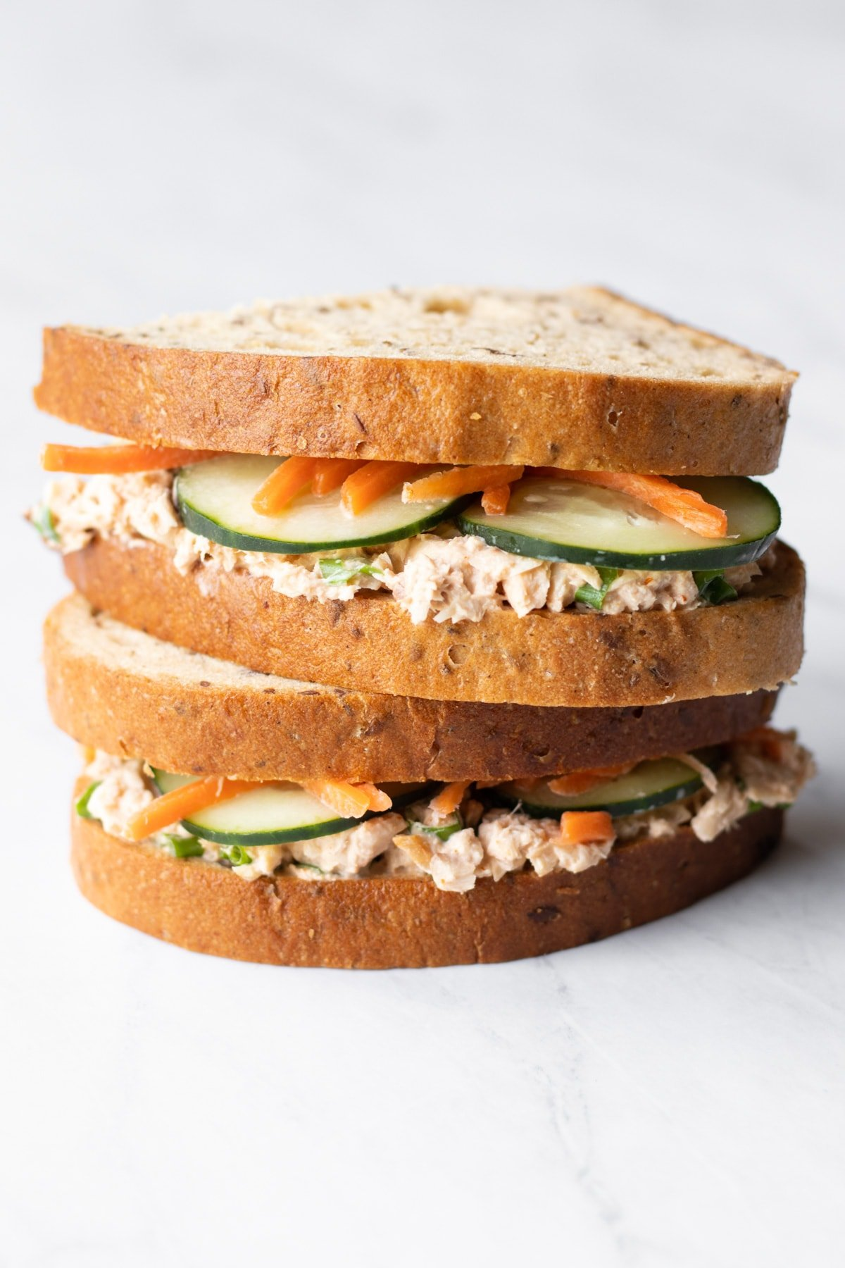 A low FODMAP spicy salmon salad sandwich is cut in two and the halves are stacked on top of each other. In between the low FODMAP bread slice spread with salmon salad, there are bits of cucumber slices and carrot matchsticks poking out.