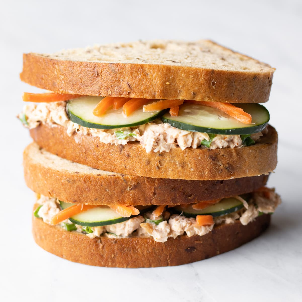 Halves of a low FODMAP spicy salmon salad sandwich are stacked on top of each other on a white marble slate.