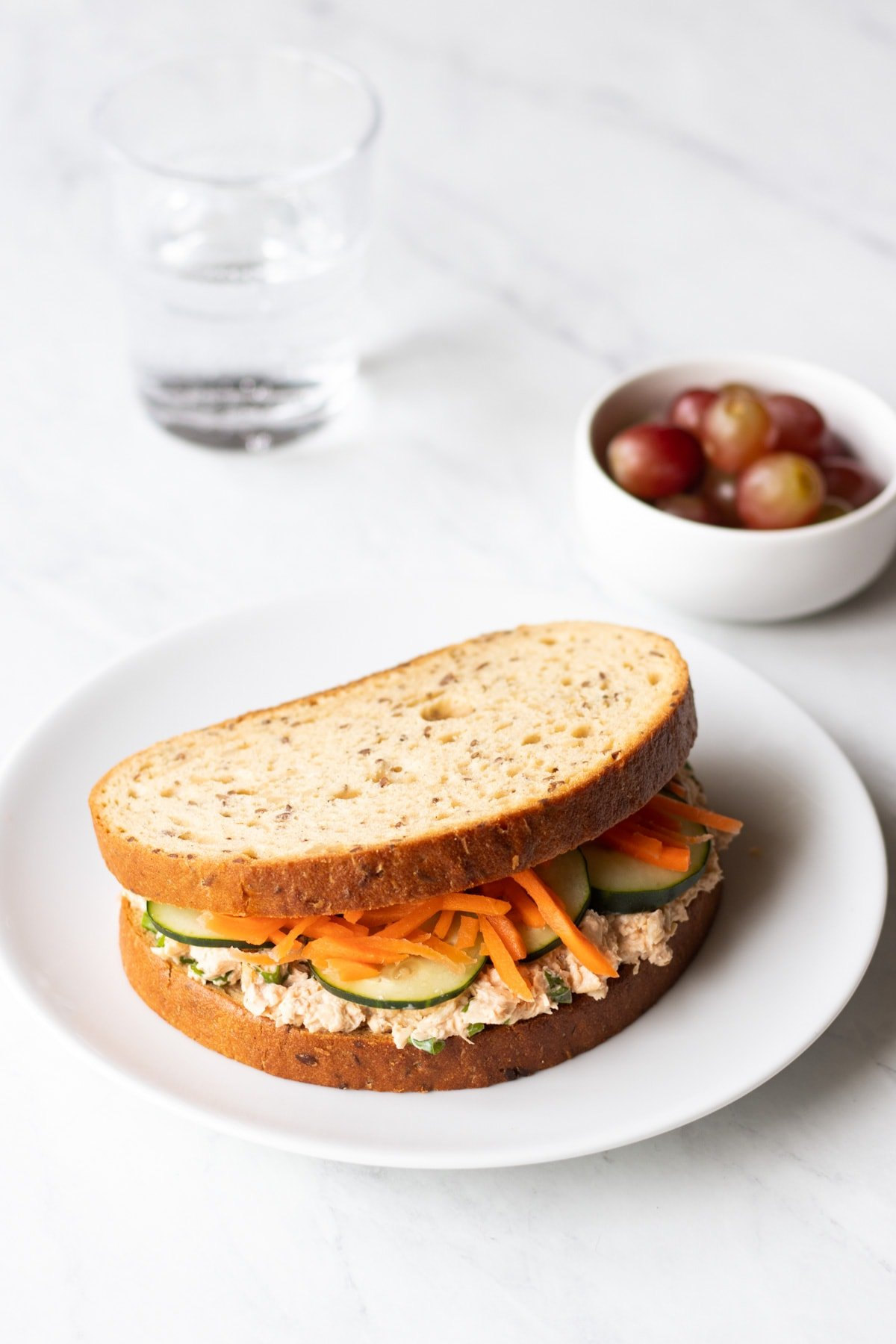 A low FODMAP spicy salmon salad sandwich on a white plate. A small bowl of red grapes and clear glass of water are in the background.