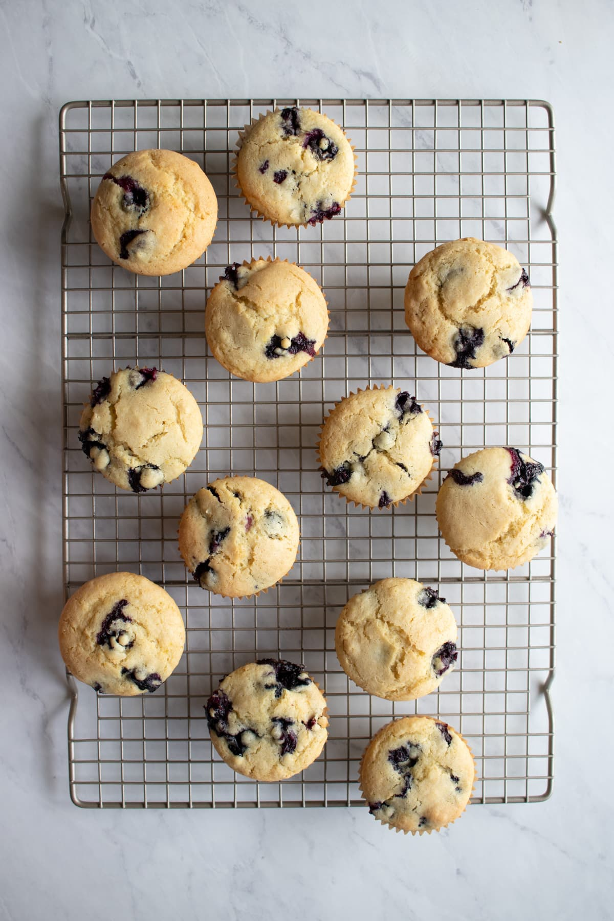 A batch of blueberry muffins on a cooling rack.