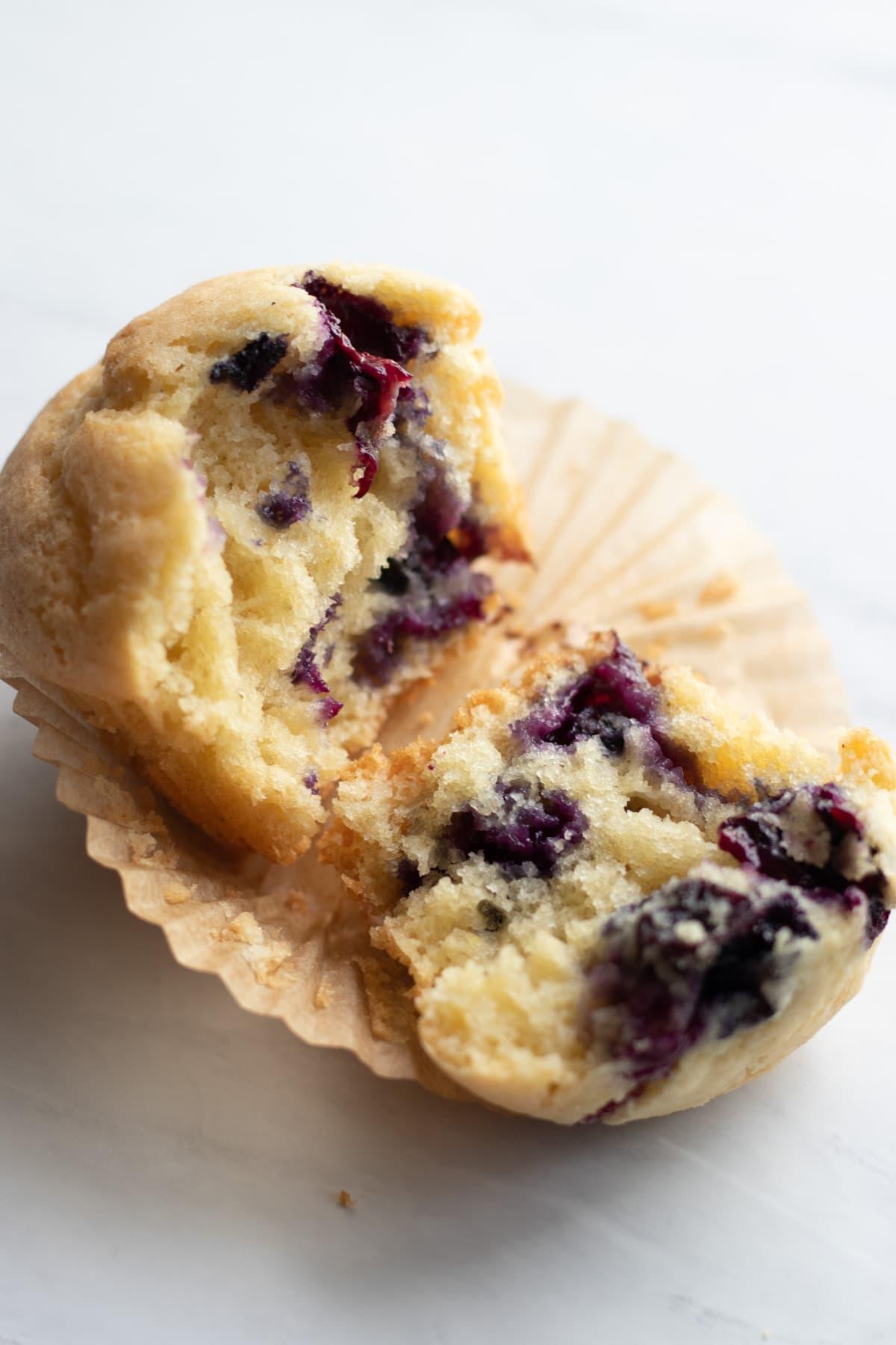 A low FODMAP blueberry muffin broken in half.