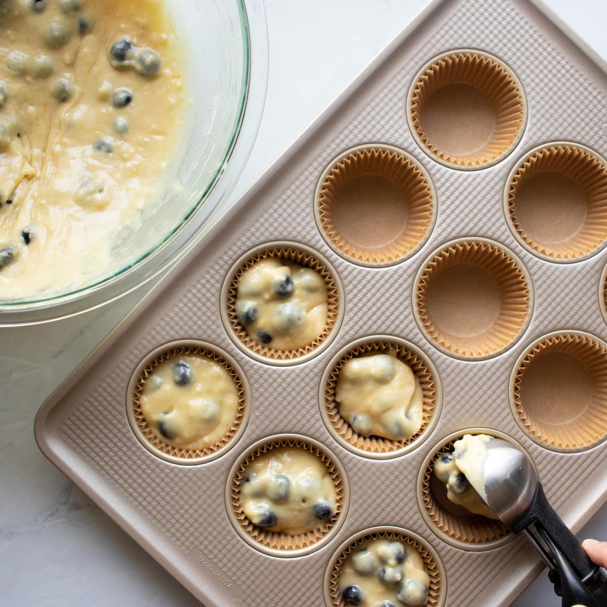 Filling muffin tin with blueberry muffin batter.