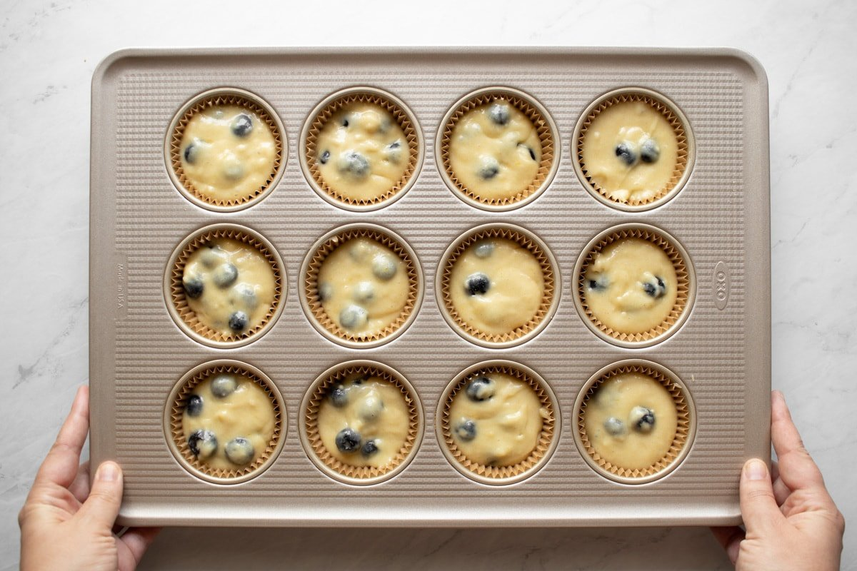 Transferring muffin tin filled with muffin batter to the oven.