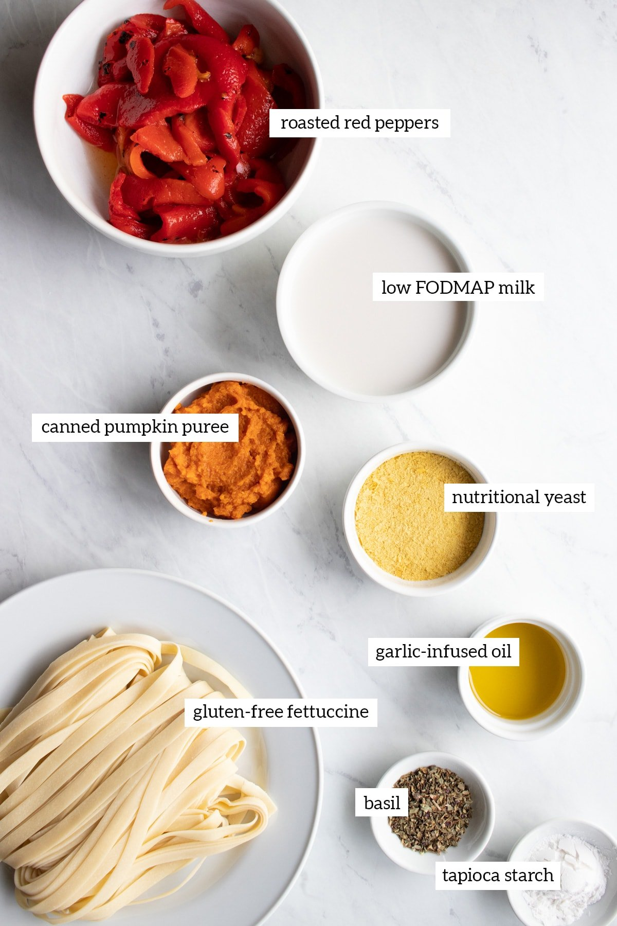 The ingredients needed for roasted red pepper pasta are measured out into individual white dishes.