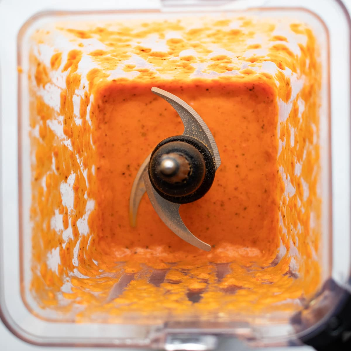 Looking down into a blender with freshly made roasted red pepper sauce.