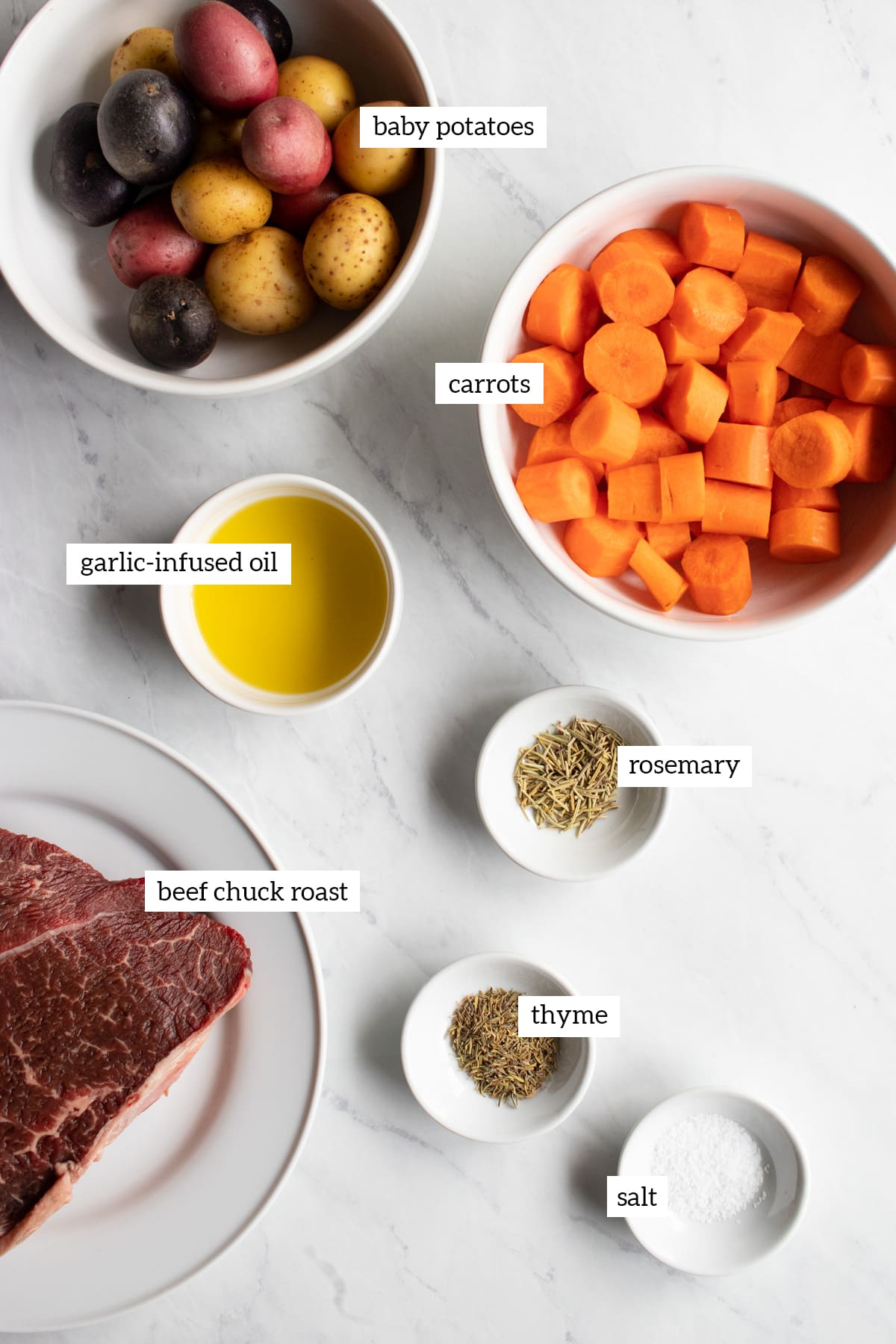 Ingredients needed to make slow cooker pot roast are measured out into small white dishes