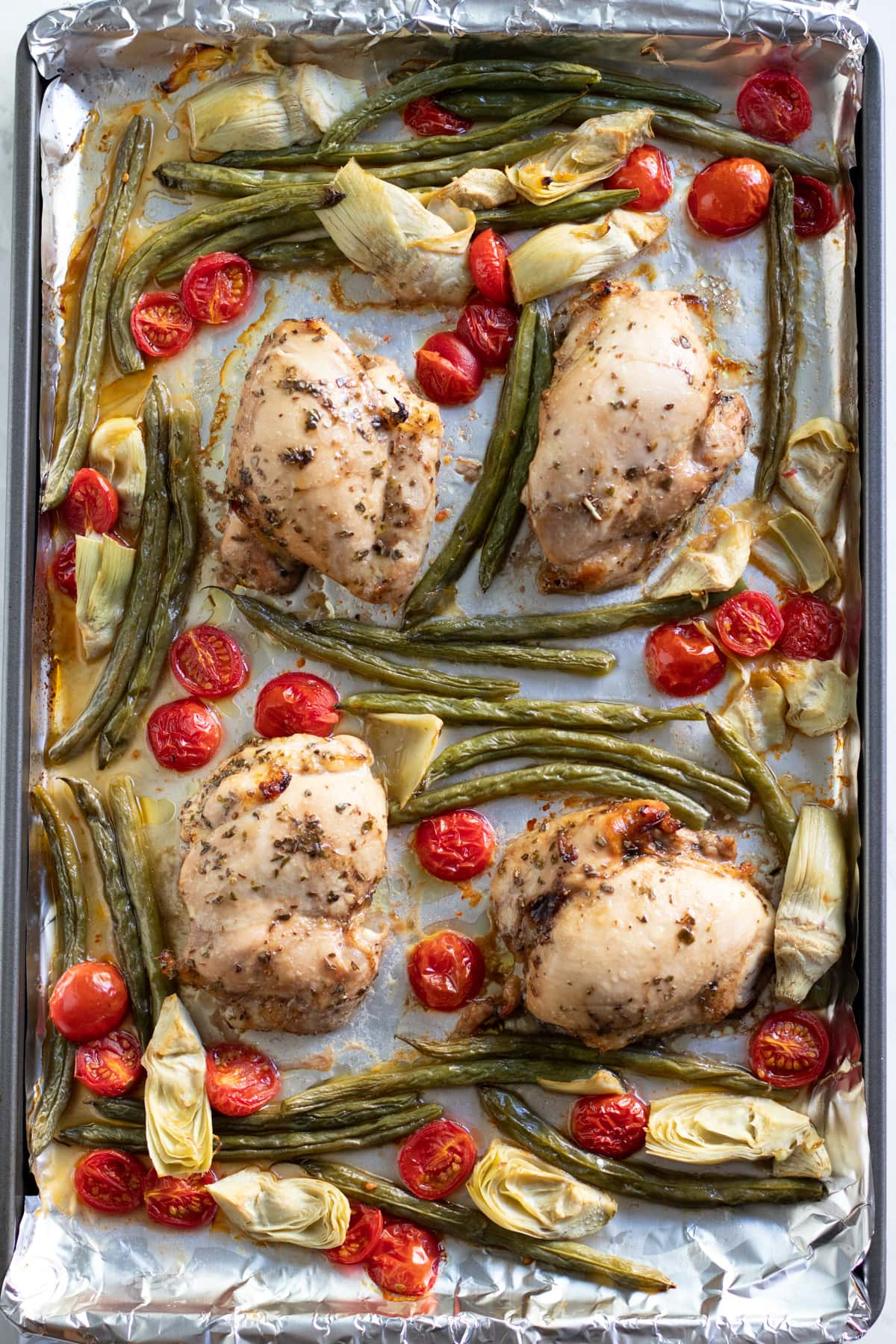 A sheet pan covered in aluminum foil with baked chicken, green beans, cherry tomatoes, and canned artichokes on top.
