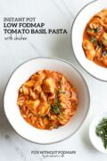 Two bowls sit on a white marble counter and are filled with pasta tossed in creamy tomato sauce. In the white space a black text overlay reads Instant Pot Low FODMAP Tomato Basil Pasta with Chicken.