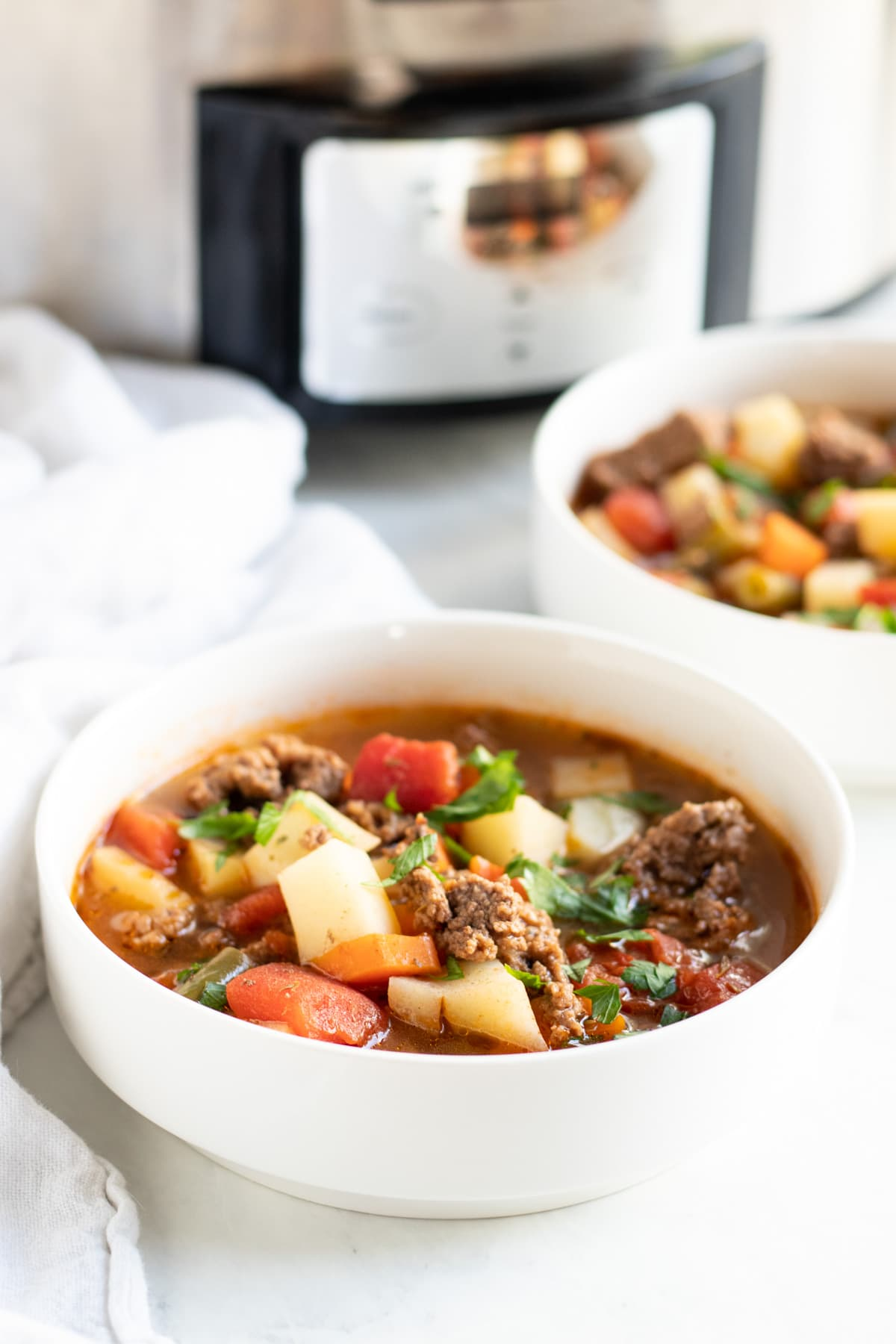 Two bowls of hamburger and veggie soup sit in front of the slow cooker where it was made.