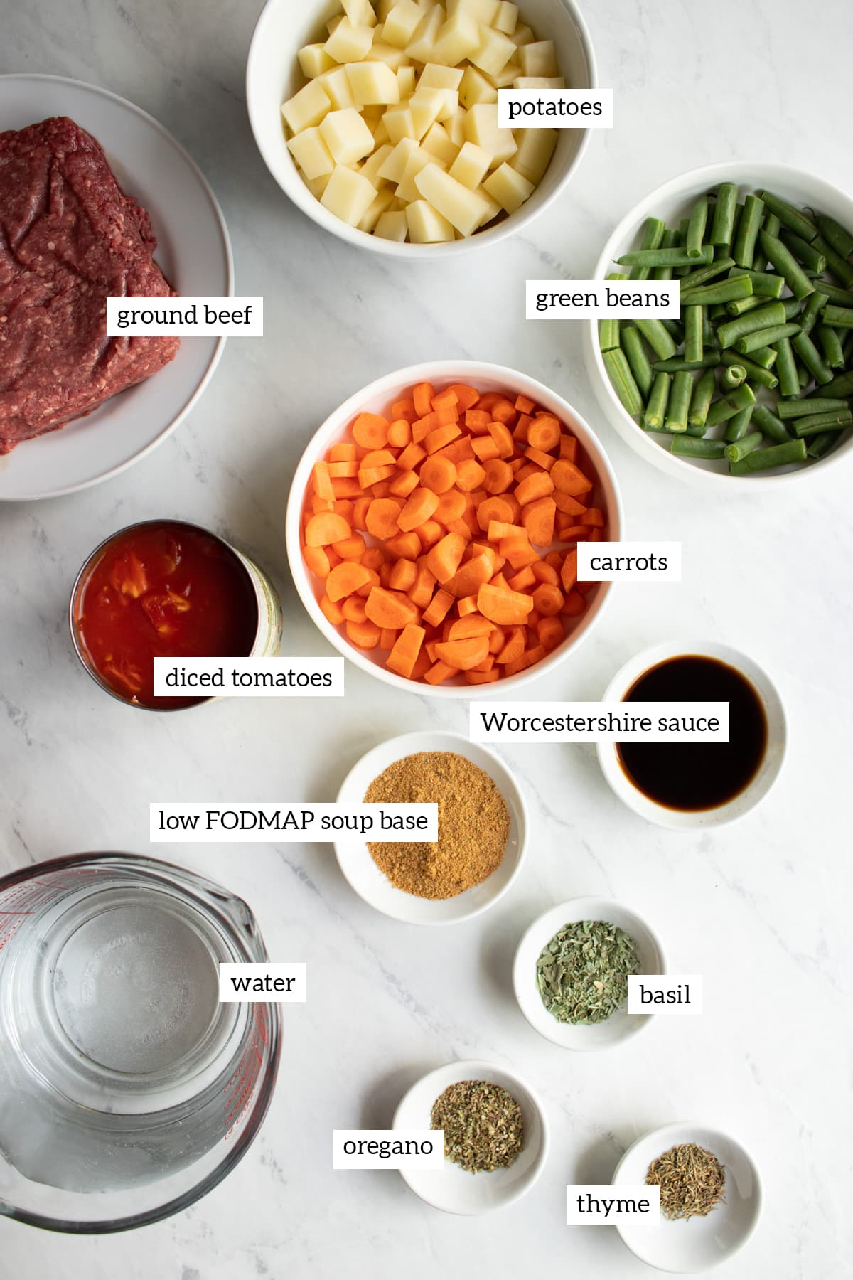 Ingredients needed to make Low FODMAP Hamburger Vegetable Soup are measured out into individual white bowls.