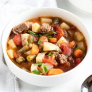 A bowl of soup made with ground beef, potatoes, carrots, tomatoes, and green beans.
