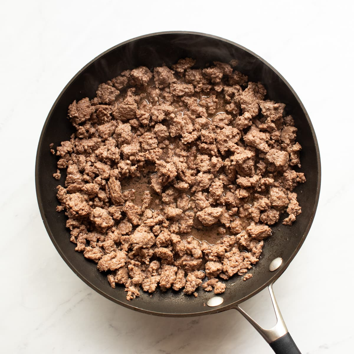 A skillet with browned ground beef.