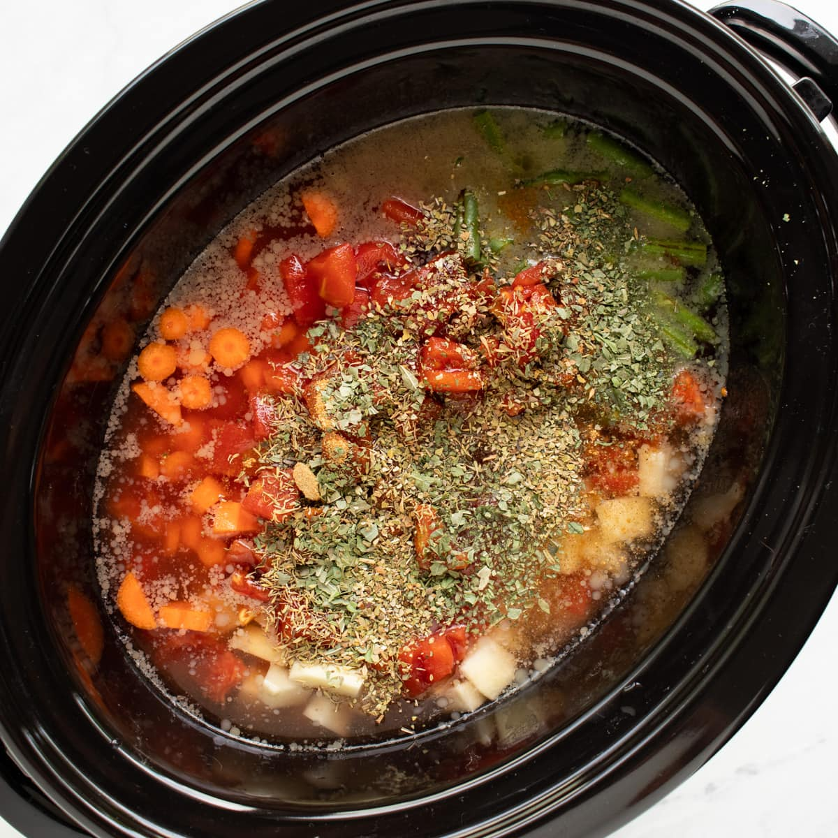 A slow cooker filled with all of the ingredients needed to make hamburger vegetable soup