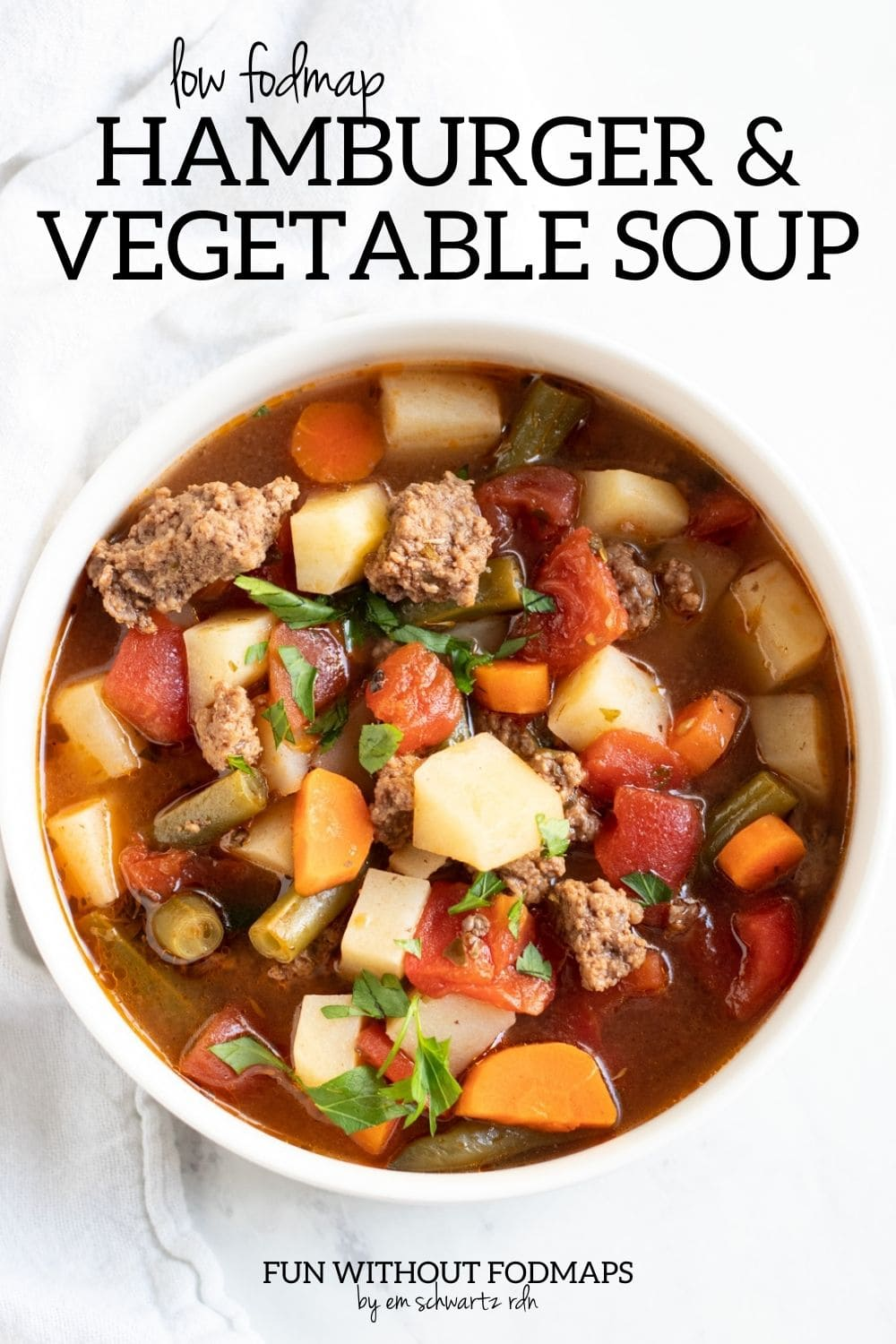 Looking down at a bowl of soup made with ground beef, potatoes, tomatoes, carrots, and green beans. In the white space above the bowl, black text reads Low FODMAP Hamburger Vegetable Soup.