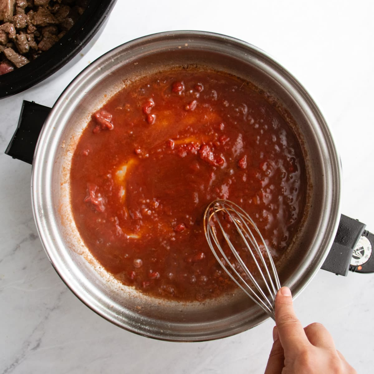 cooking down tomato paste and red wine in a skillet