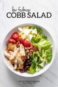 "A bowl filled with lettuce, bacon, chicken, hard-boiled eggs, cherry tomatoes, and kalamata olives. Above the bowl, black text reads ""Low FODMAP Cobb Salad."""