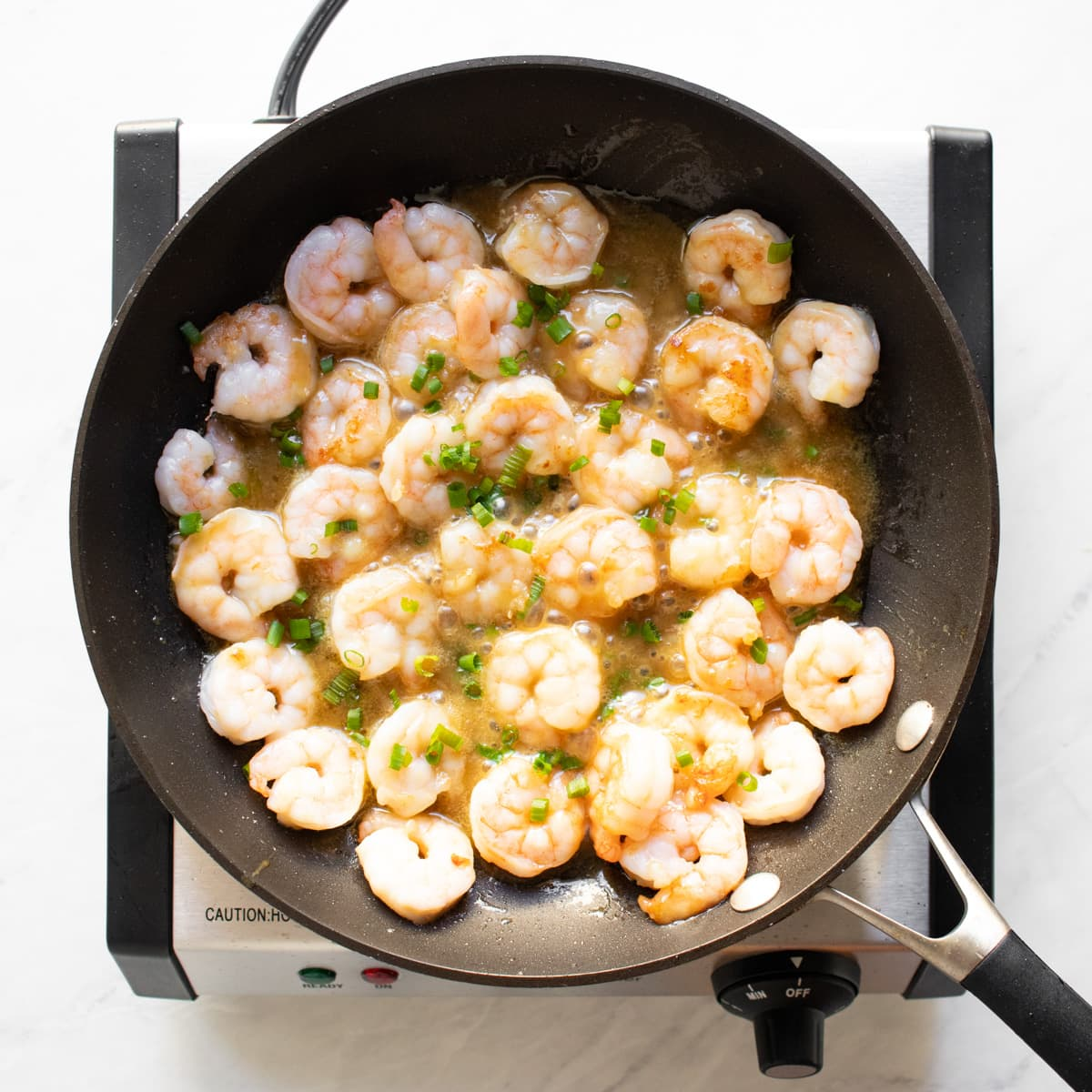 Cooked maple dijon shrimp topped with snipped chives.