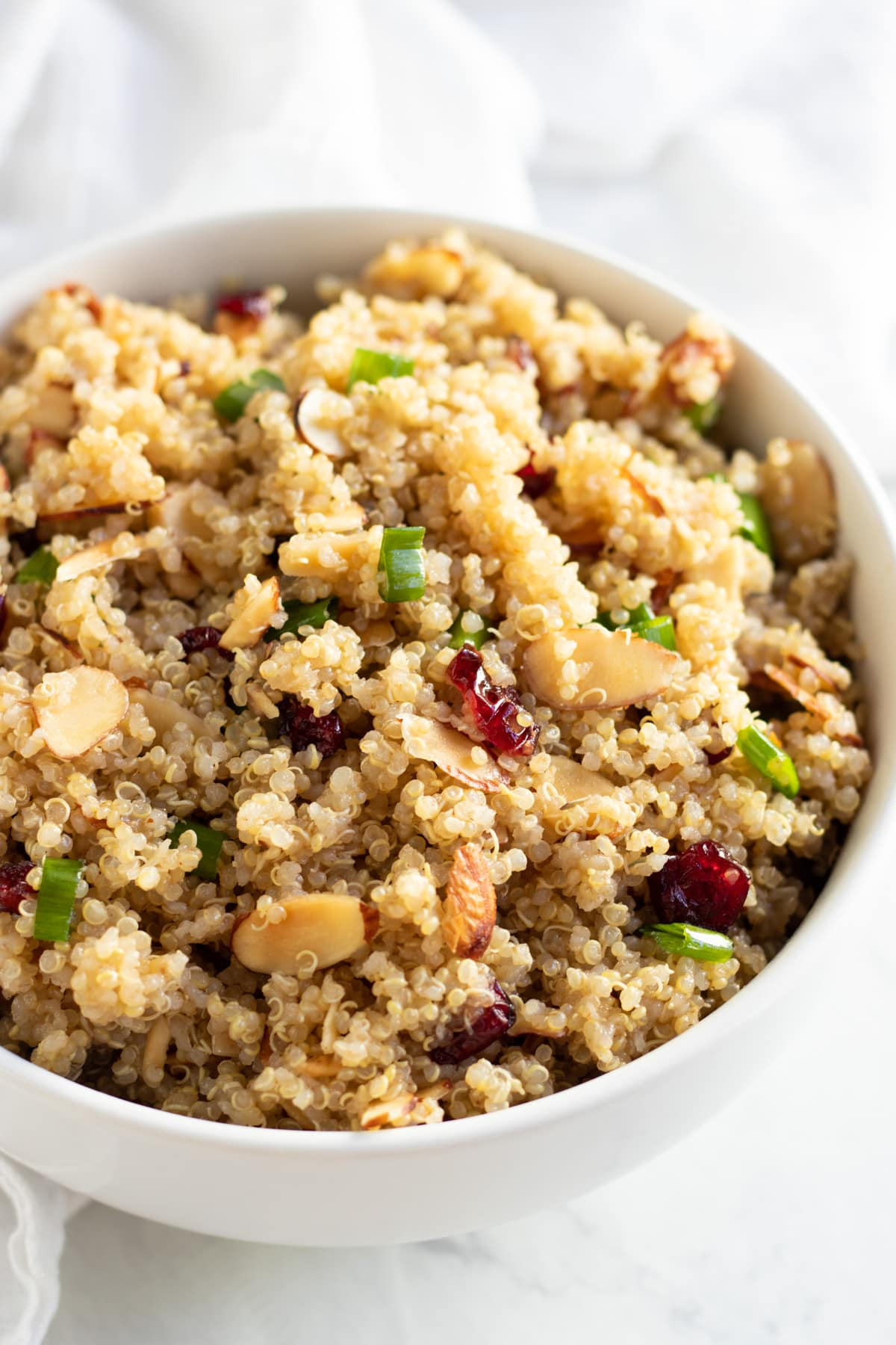 A close up of a quinoa salad dotted with dried cranberries, toasted almond slices, and sliced green onion tops.