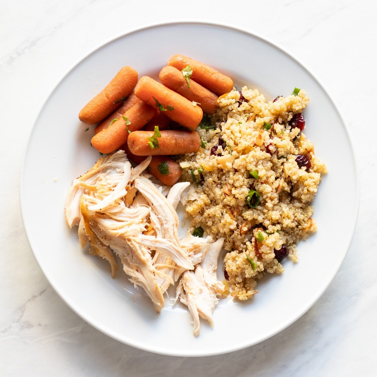 A plate with roasted chicken, quinoa salad with cranberries and almonds, and cooked carrots.