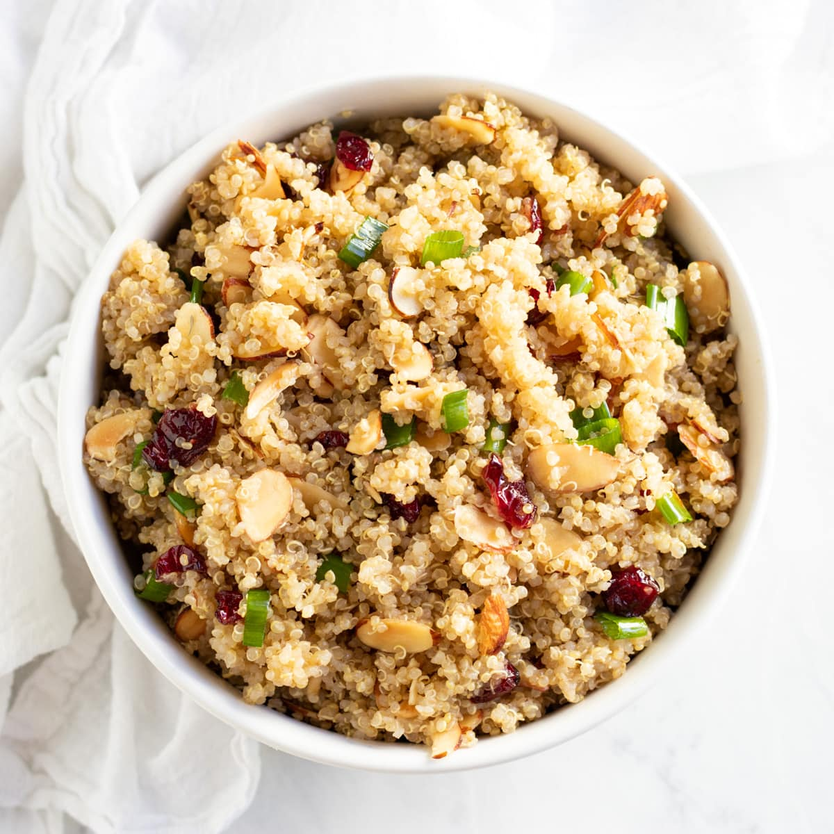 A white bowl filled with low FODMAP quinoa with cranberries and almonds