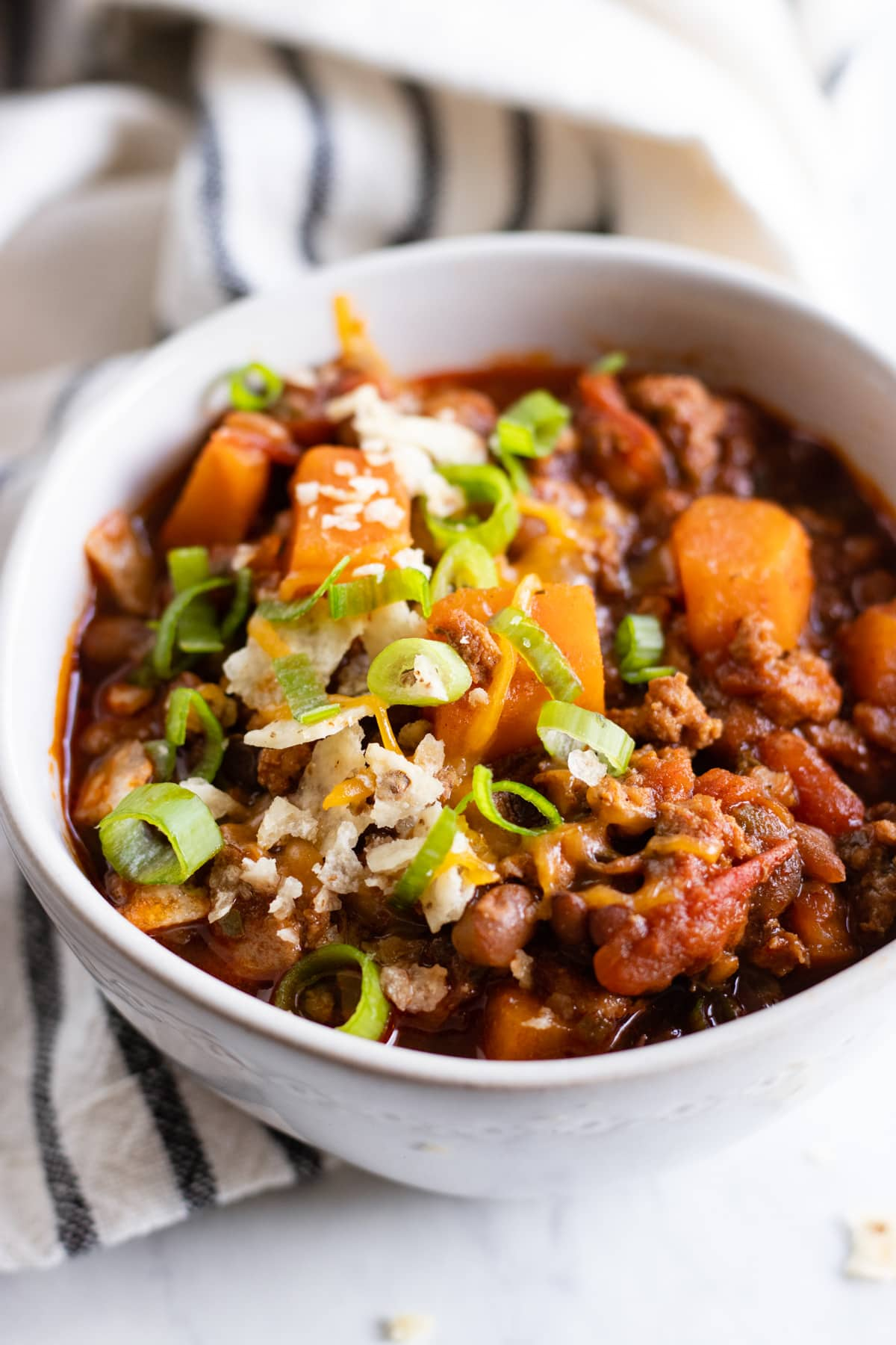 A bowl of chili made with ground turkey, sweet potatoes, and canned lentils and topped with crushed corn tortilla chips and sliced green onion tops.