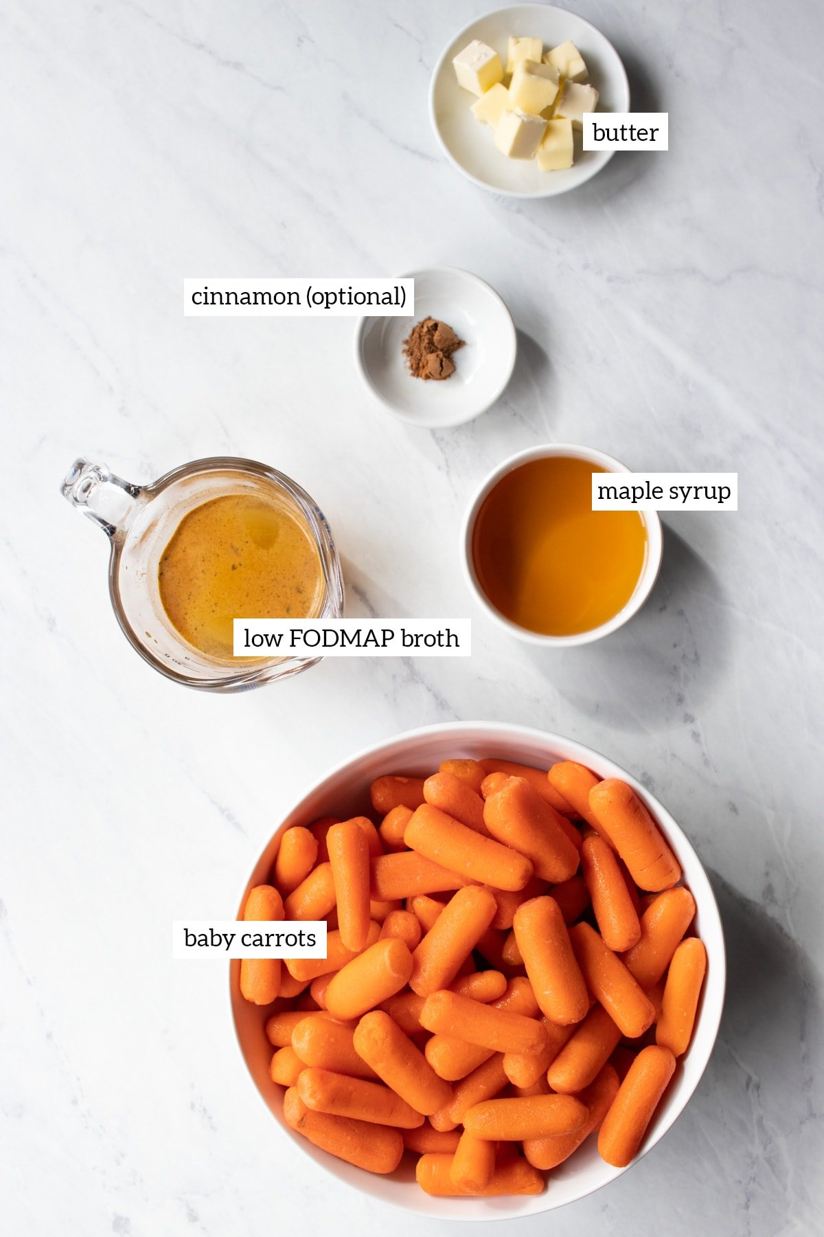 Ingredients needed for Slow Cooker Low FODMAP Maple-Infused Carrots are measured out into individual white bowls.