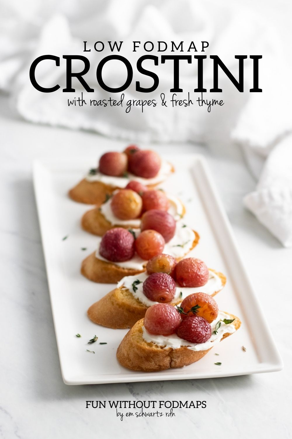 "A white serving platter with 5 toasted baguette slices topped with lactose-cream cheese, roasted grapes, and fresh thyme. In the white space above the platter, black text reads ""Low FODMAP Crostini with roasted grapes & fresh thyme"""