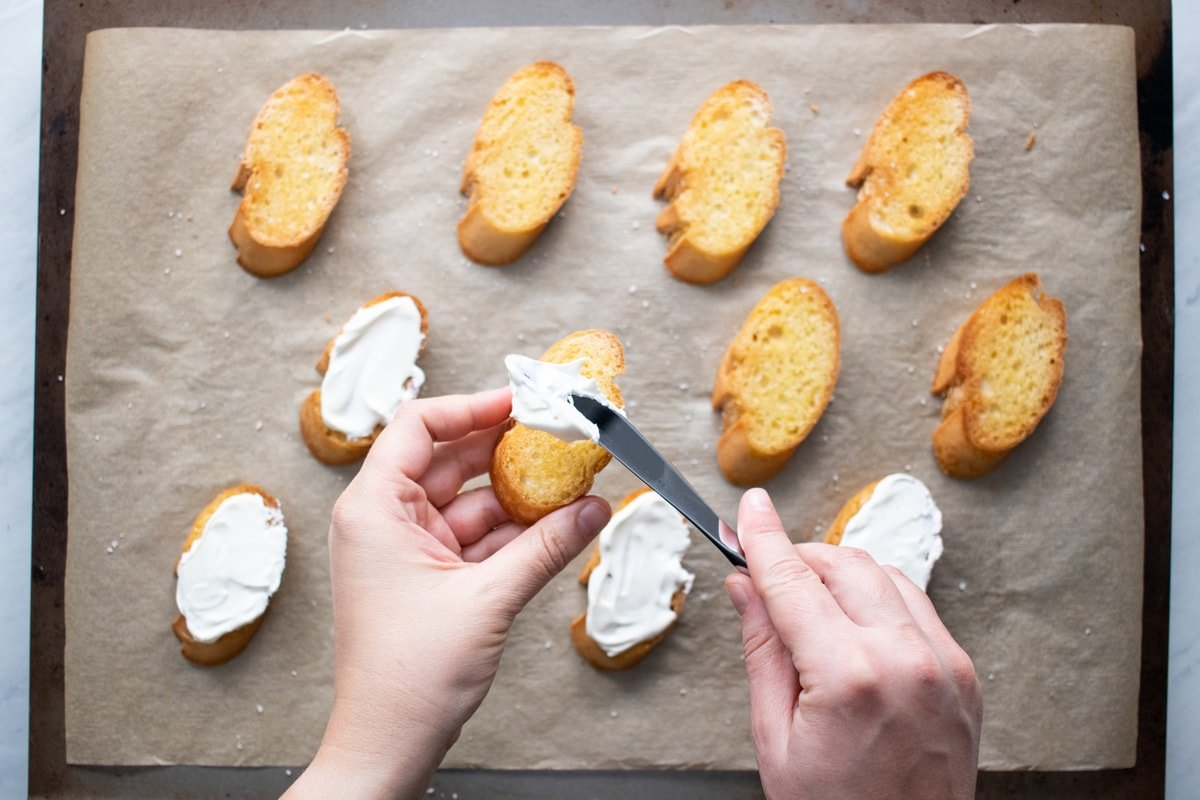 Lactose-free cream cheese being spread onto toasted baguette slices.