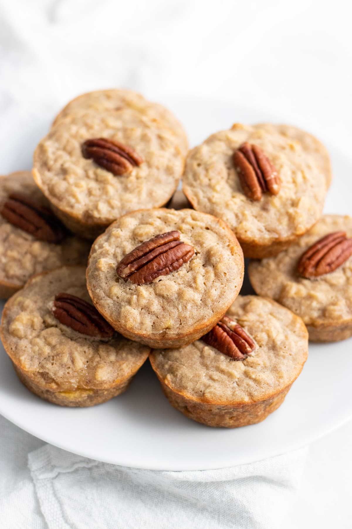 A plate of stacked baked oatmeal cups. Each oatmeal cup is topped with a pecan halve.