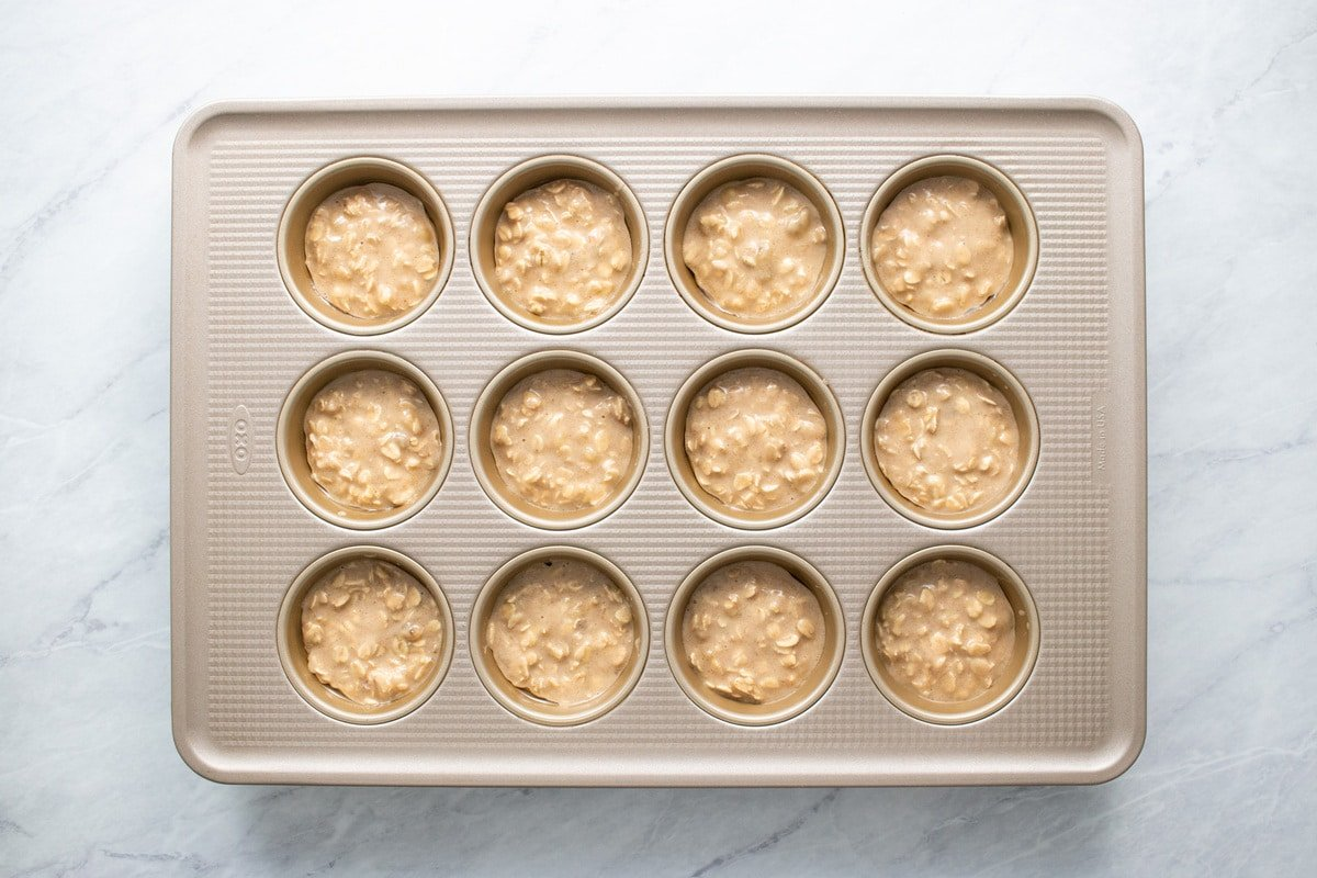 The batter is divided evenly into a muffin tin.