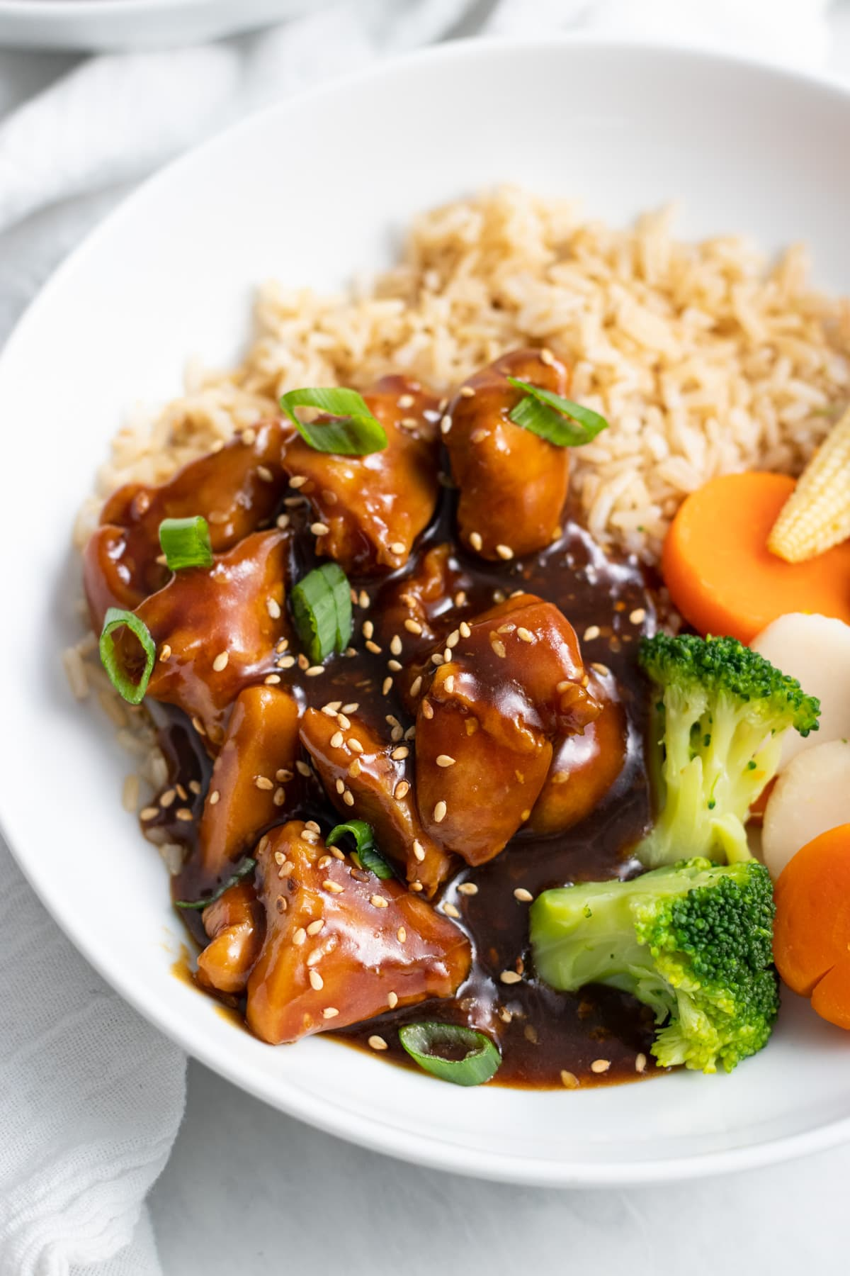 A close-up of low FODMAP sesame chicken topped with sliced green onion tips and toasted sesame seeds.
