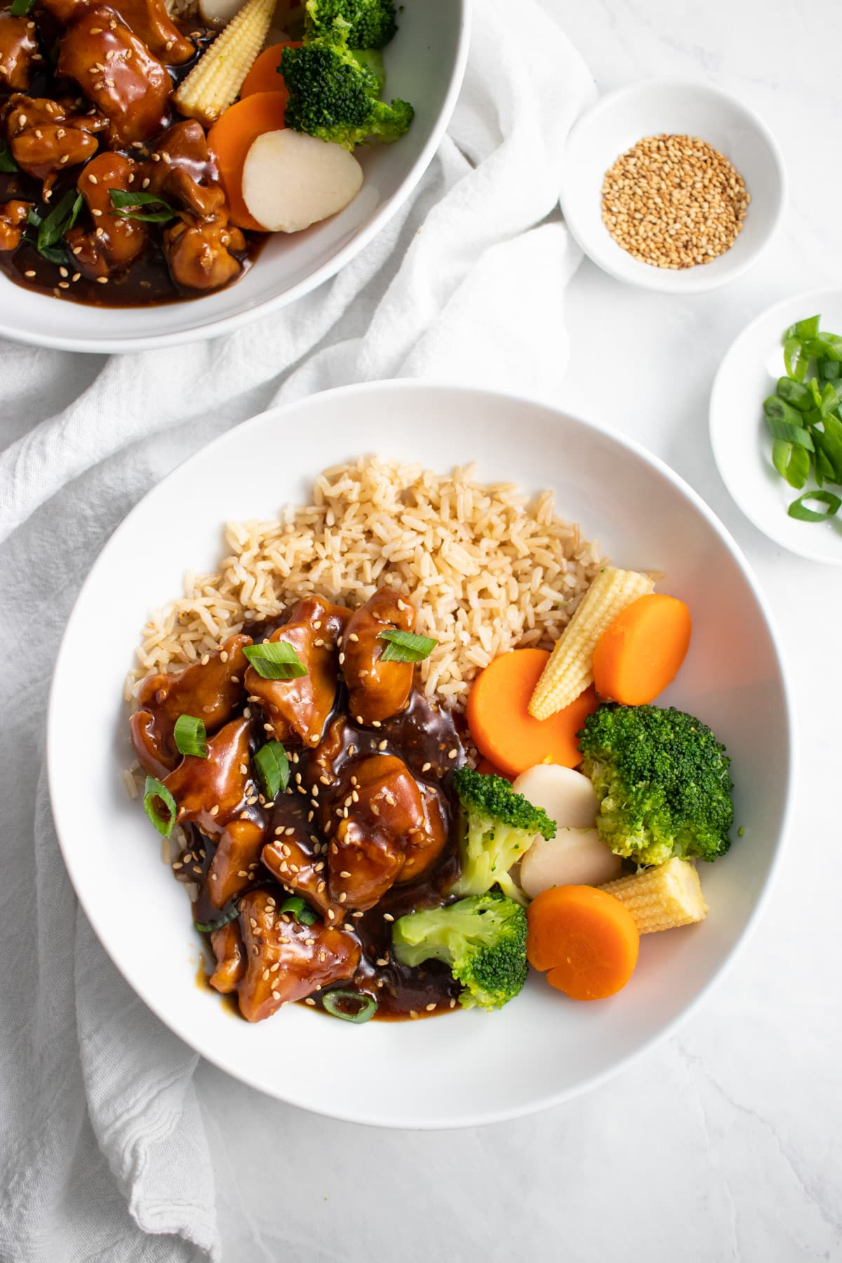 Looking down at a bowl of sesame chicken served with brown rice and steamed veggies. A second bowl of chicken, as well as small bowls of toasted sesame seeds and sliced green onion tops sit above it.