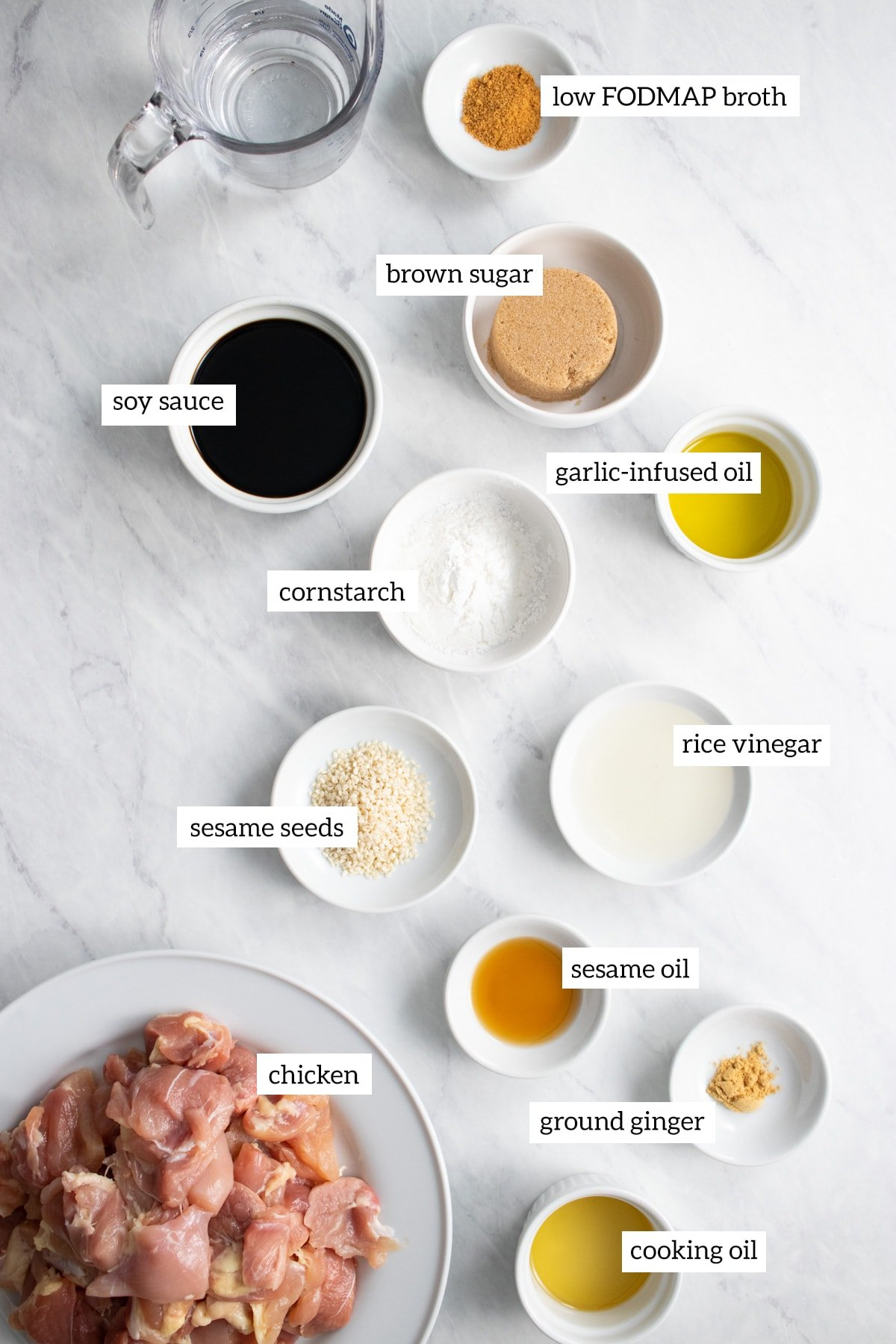 Ingredients needed for sesame chicken measured out into individual white bowls.