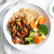 A bowl of low FODMAP sesame chicken, steamed mixed veggies, and brown rice