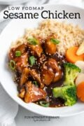 """A bowl of low FODMAP sesame chicken, steamed mixed veggies, and brown rice. A black text overlay above it reads """"Low FODMAP Sesame Chicken."""""""