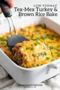 """A spatula lifting a serving of cheesy casserole out of a baking dish. Above in the white space, black text reads """"Low FODMAP Tex-Mex Turkey and Brown Rice Bake."""""""