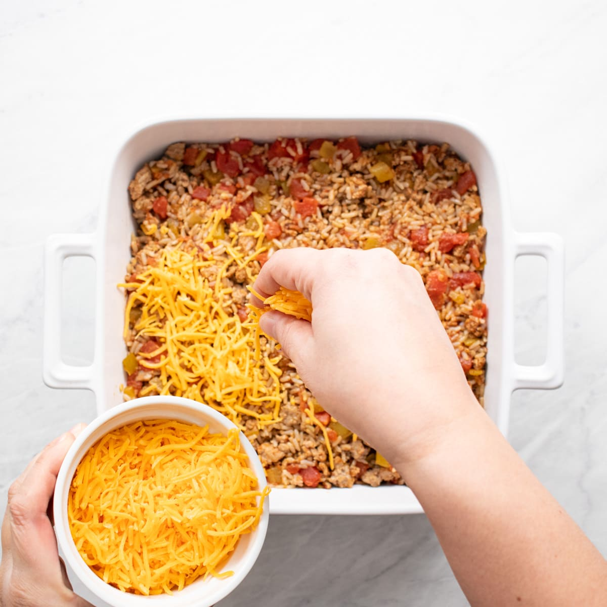 Sprinkling shredded cheddar cheese onto brown rice and turkey mixture in baking dish.