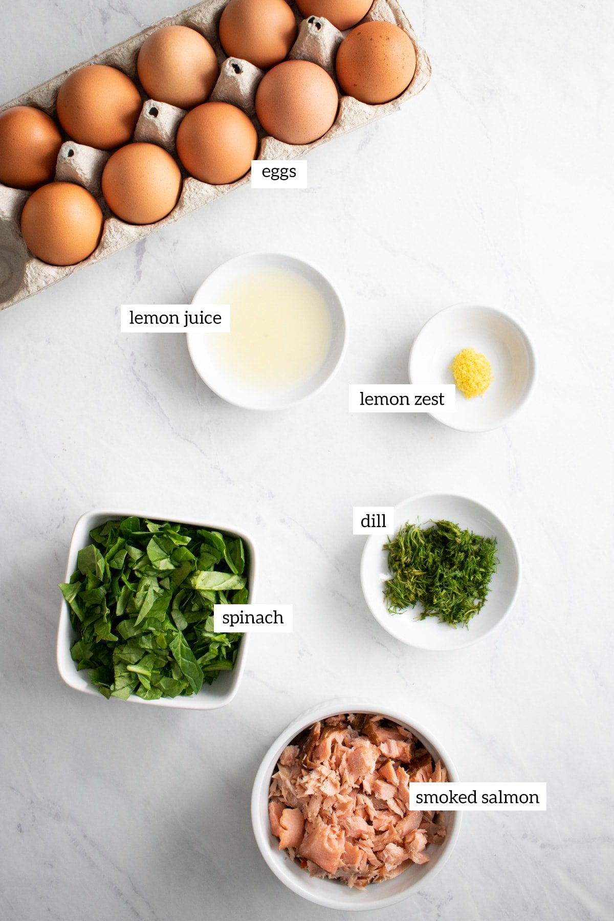 Ingredients for low FODMAP smoked salmon and spinach frittata cups are measured out into individual bowls