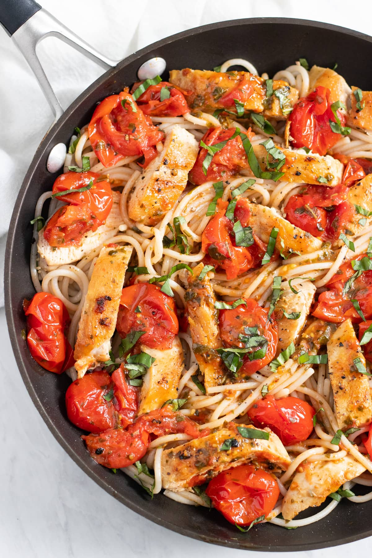 Skillet with pan-fried chicken strips, burst cherry tomatoes, and spaghetti in a white-wine butter sauce. Everything is topped with thinly-sliced fresh basil.