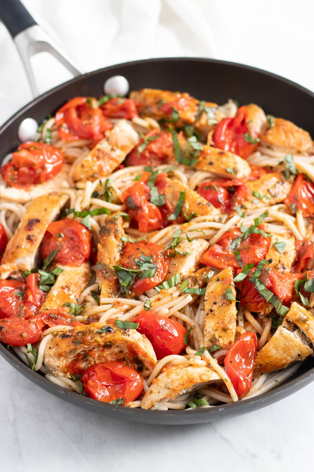 A black skillet filled with a cooked pasta dish made with spaghetti, cherry tomatoes, chicken, and basil.