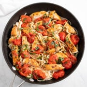 A skillet filled with spaghetti, crushed cherry tomatoes, and cooked chicken slices.