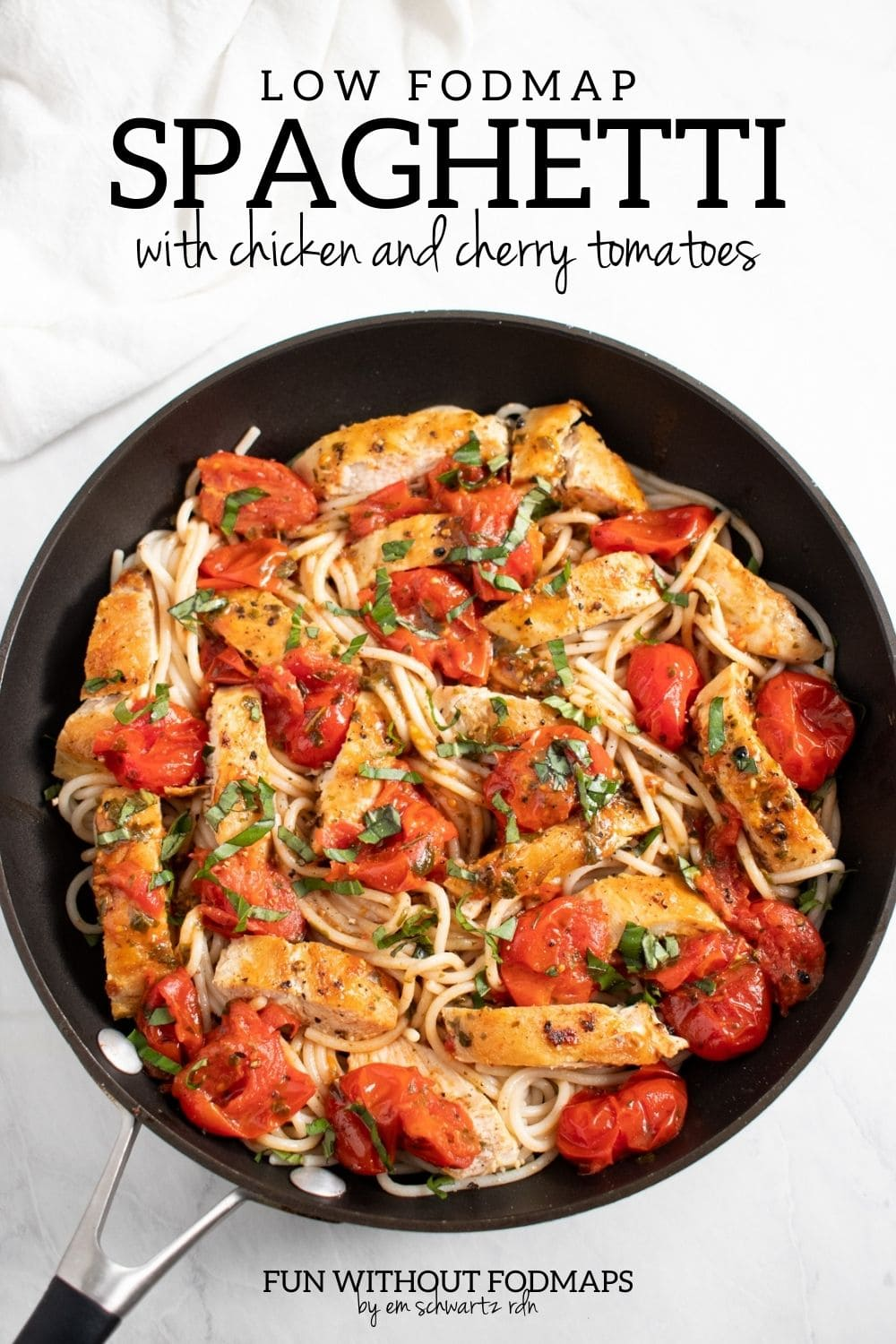 """Looking down at a skillet filled with a cooked pasta dish dotted with cherry tomatoes, sliced chicken, and fresh basil. In the white space above, black text reads """"Low FODMAP Spaghetti with Chicken and Cherry Tomatoes."""""""