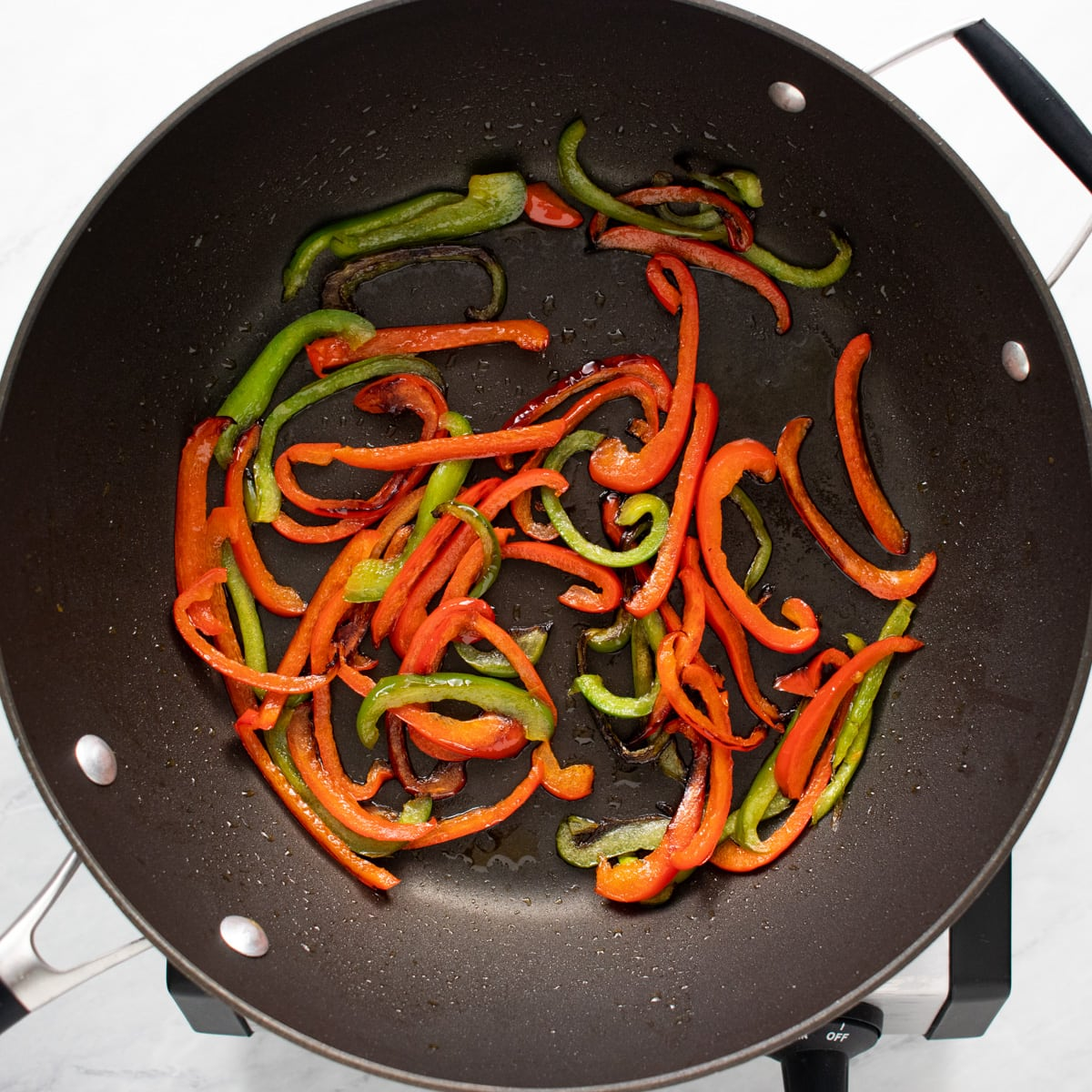 A skillet with sautéed slices of red and green bell pepper.